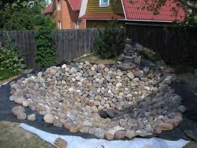 Украшение дна водоема, выложенного агроволокном, речными камнями