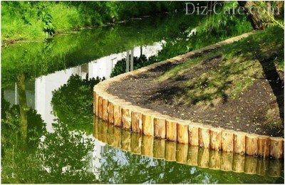 Аккуратный ряд бревен лиственницы подчеркивает красоту берега водоема