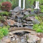Каскадный водопад и мостик через него в саду