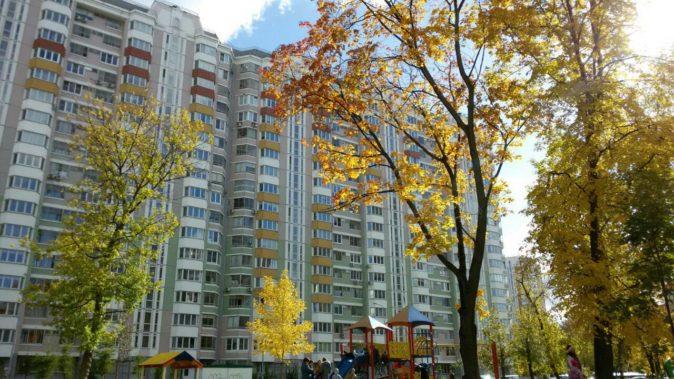 Многоквартирный дом и двор на фоне деревьев