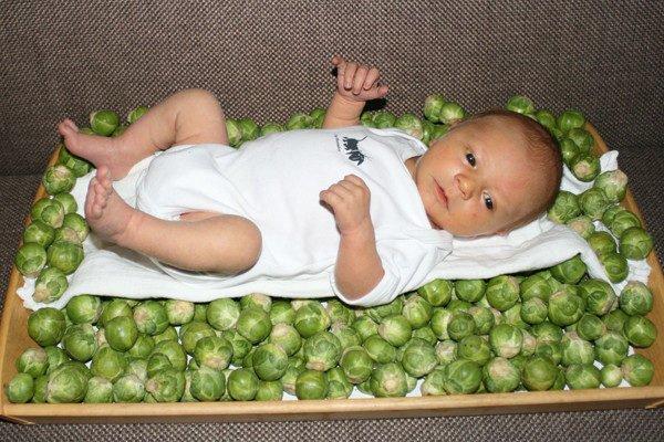 Младенец лежит в ящике с брюссельской капустой
